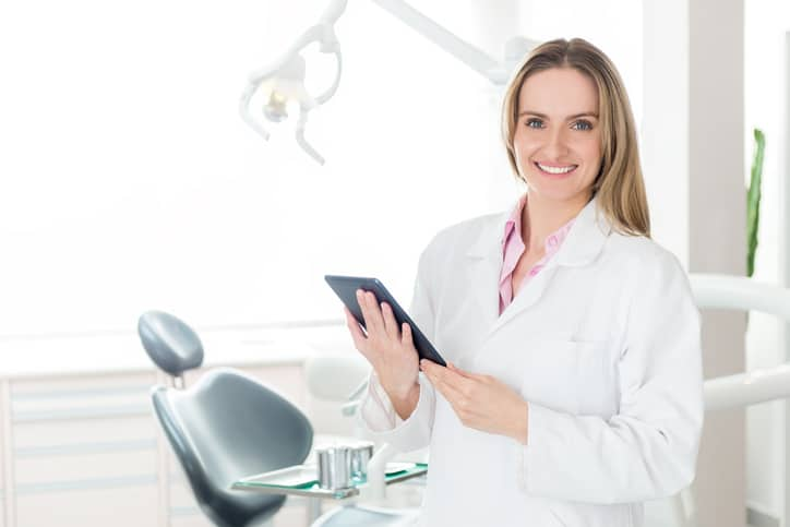 Horizontal color image of female dentist holding digital tablet in dental clinic office, smiling and looking at camera. Female doctor wearing white uniform. Dental equipment in the background.
